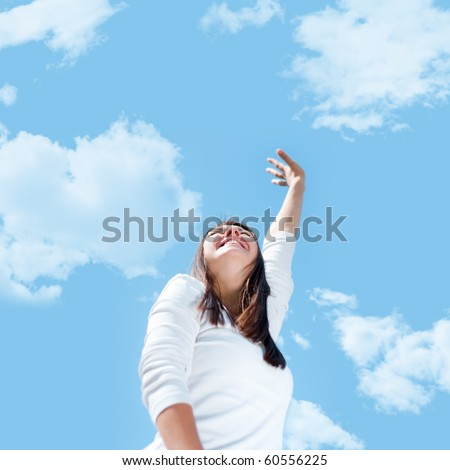 A young woman stretches her hand towards the sky. - stock photo