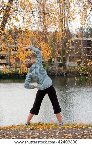 A young woman stretching by a river - stock photo