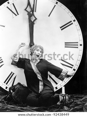 A young woman stretching in front of a giant clock striking midnight - stock photo
