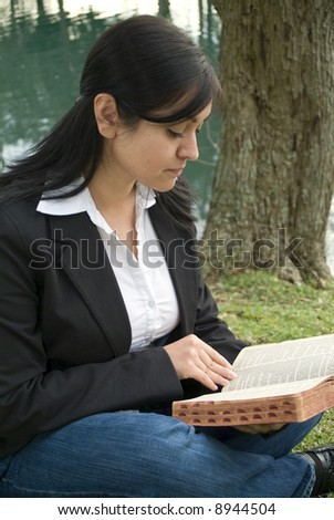 A young woman student sitting outside reading or studying a bible or book. - stock photo