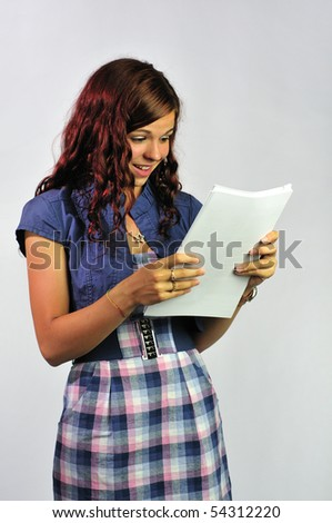 A young woman studying a printed document and expressing delight. - stock photo