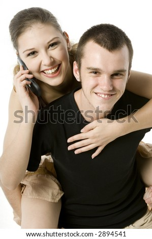 A young woman takes a piggyback and a phonecall on white background - stock photo