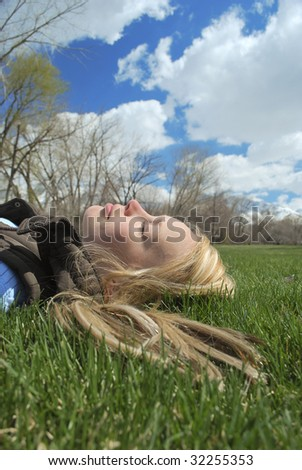 A young woman taking a nap in the park on a spring day. - stock photo