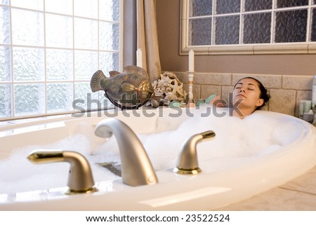 A young woman taking a relaxing bubble bath - stock photo