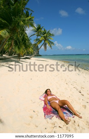 A young woman taking a sun bath in a desertic caribbean beach. It is Playa Fronton in Samana, Dominican Republic.
