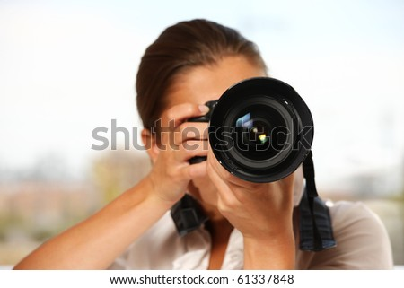 A young woman taking pictures over white background