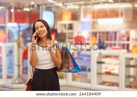 A young woman talking on the phone in a shopping mall - stock photo