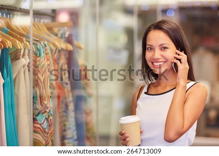 A young woman talking on the phone while browsing for clothes in a shop - stock photo