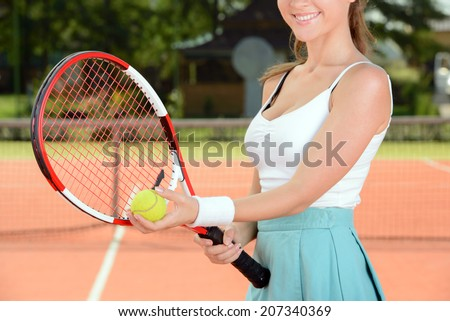 A young woman tennis player during a game of tennis on the tennis court - stock photo