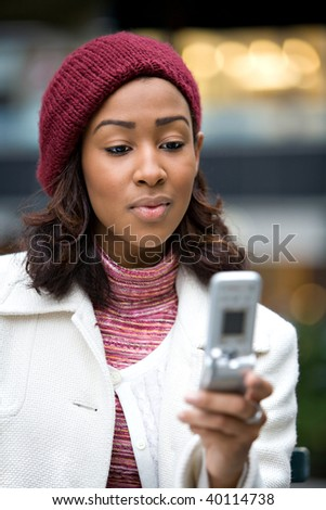 A young woman text messaging or checking email on her wireless phone. - stock photo