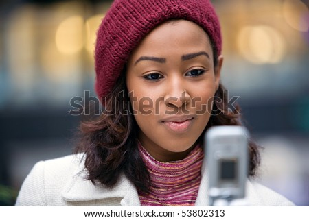 A young woman text messaging or checking something on her wireless phone. - stock photo