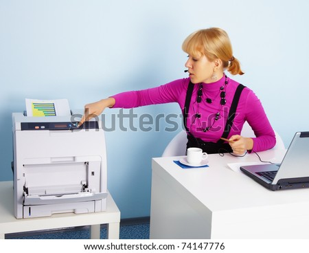A young woman - the secretary prints out a color document