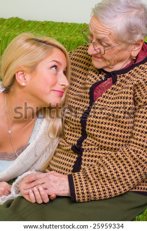 A young woman  together whit an older one talking, smiling at her - part of a series. - stock photo