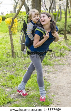 A young woman trekking with her baby pointing somewhere - stock photo