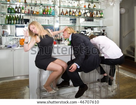 A young woman turning down a flirting male at a bar with a sleeping drunk next to them - stock photo