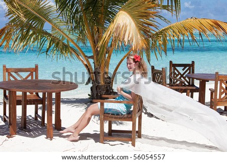 A young woman underneath a palm enjoying the sunshine on a wonderful island