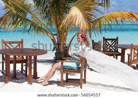A young woman underneath a palm enjoying the sunshine on a wonderful island - stock photo