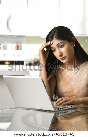 A young woman uses a laptop on a kitchen table. She has a worried expression on her face. Vertical shot. - stock photo