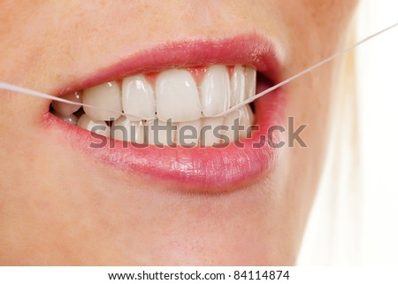 A young woman uses dental floss to clean your teeth