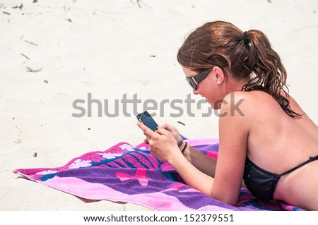 A young woman using her cell phone at the beach - stock photo