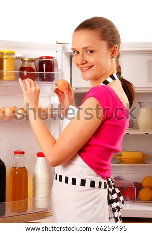 A young woman using the refrigerator, reaching for eggs. Food, milk, red wine and juice in the background. - stock photo