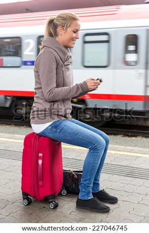 a young woman waiting for a train and writes with her cell phone a sms - stock photo