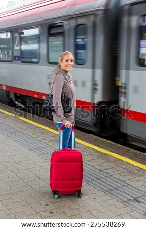 a young woman waiting for a train at a station. train holidays - stock photo