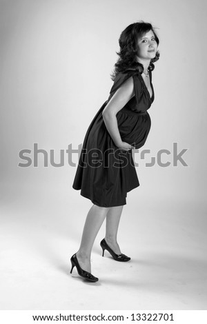 A young woman waiting for her baby, posing for photographer at studio.