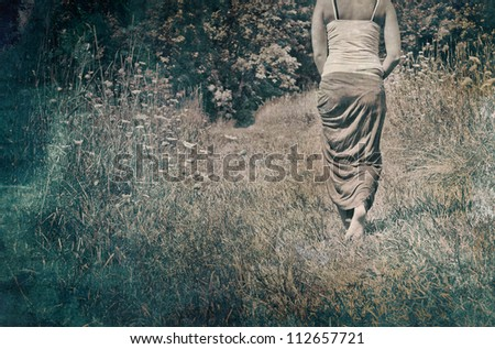 A young woman walking away along a nature path. - stock photo