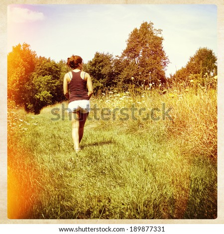 A young woman walking away along a nature path, instagram style filter