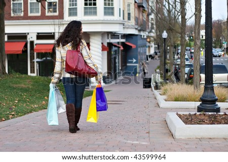 A young woman walking in the city doing some shopping. - stock photo