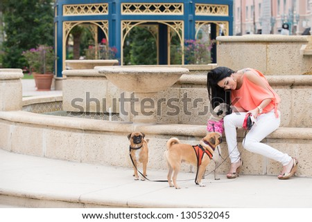 A young woman walking three dogs of pug breed.