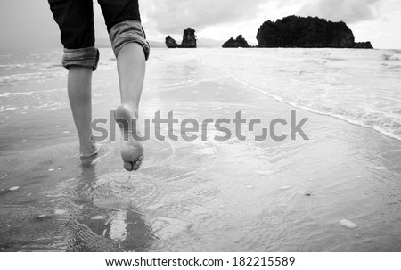 A young woman walks alone on a beach in black and white