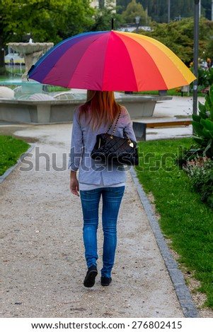 a young woman walks with a colorful umbrella in his hand walking in the rain. - stock photo