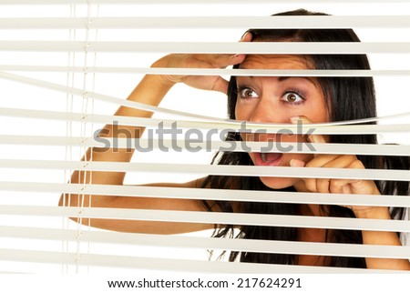 a young woman watching something through the blinds of her window - stock photo