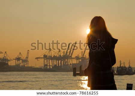 A young woman watching the sun go down over Hamburg - stock photo
