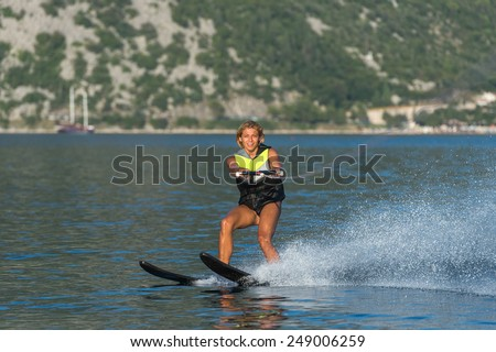 a young woman water skiing on a sea  - stock photo