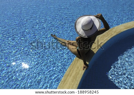 A young woman wearing a bikini and a white hat sits at the edge of a swimming pool. - stock photo