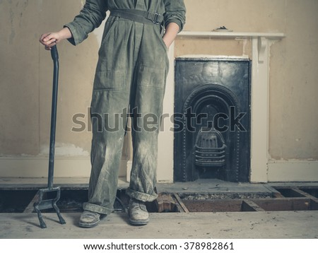 A young woman wearing a boiler suit is standing by a fireplace in a Victorian house with a crowbar in her hand