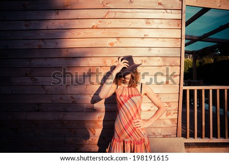 A young woman wearing a cowboy hat is standing outside a wooden cabin - stock photo