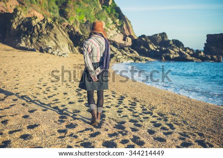 A young woman wearing a furry deerstalker hat is walking on the beach on a sunny autumn day - stock photo