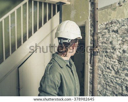A young woman wearing a hard hat and a boiler suit is standing in a house that is undergoing renovations