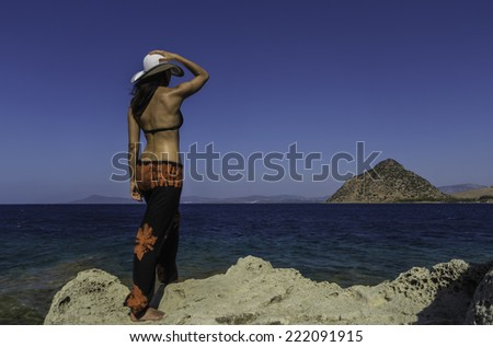 A young woman wearing a hat looks out across the sea - stock photo