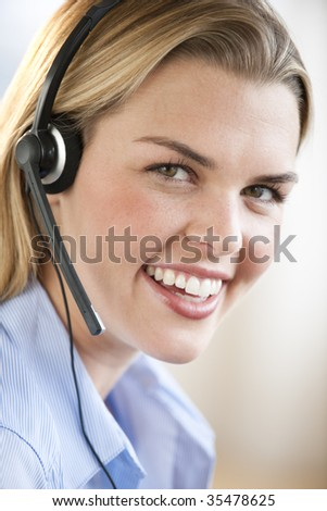 A young woman wearing a headset is smiling at the camera.  Vertically framed shot. - stock photo