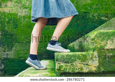 A young woman wearing a skirt is walking up some stairs by the sea covered in green moss - stock photo