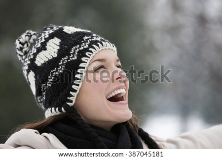 A young woman wearing a woolen hat, enjoying the open air - stock photo