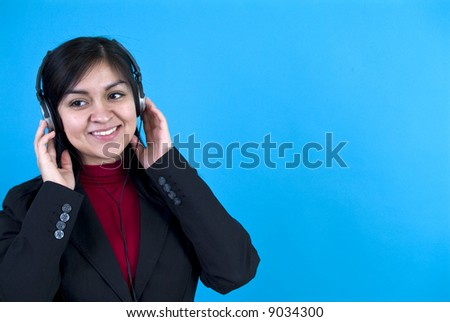 A young woman wearing headphones standing in front of a blue background with copy space. - stock photo