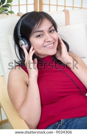 A young woman wearing headphones with a look of contentment on her face. - stock photo