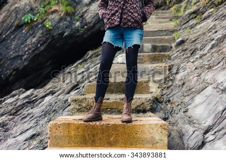 A young woman wearing hiking boots is standing on some concrete steps outdoors amongst the rocks