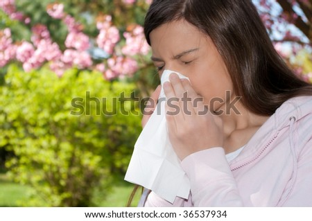 A young woman with a allergy sneezing into handkerchief. - stock photo